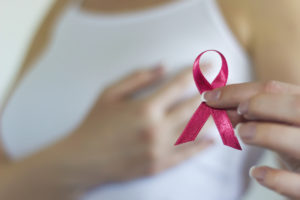 Woman hold pink ribbon for breast cancer awareness
